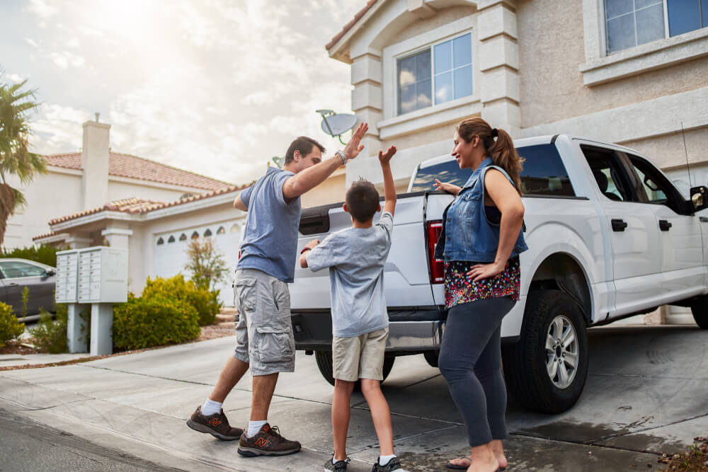 happy family highfiving with a pickup truck and home in the background