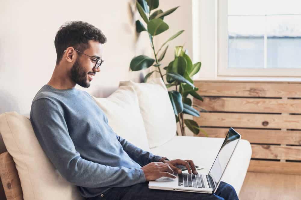 hombre joven hispano buscando seguro de auto en estados unidos en su laptop