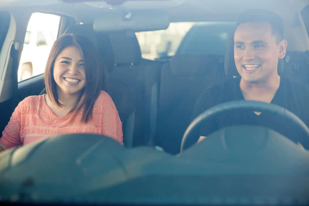 hombre y mujer en auto sonriendo