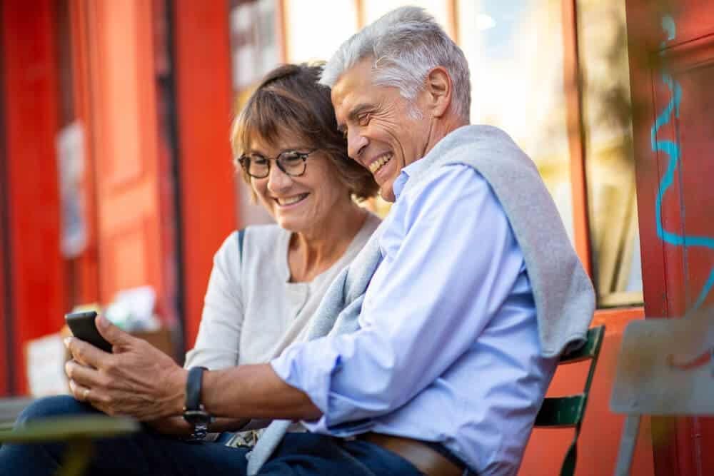 pareja hispana mayor sonriendo mientras buscan aseguranza de auto barata en su celular