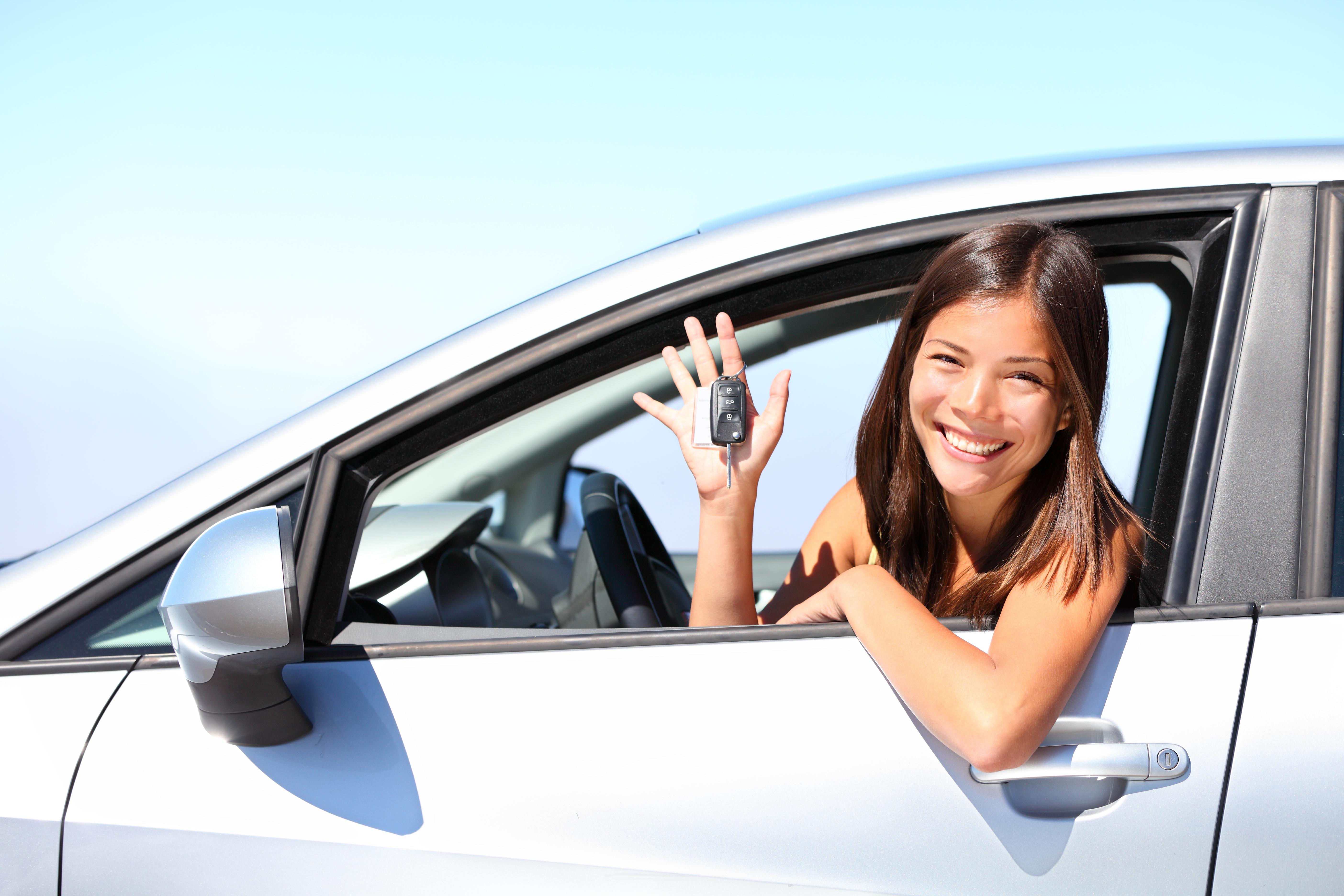 mujer_feliz_en_auto_blanco_con_llaves_en_mano