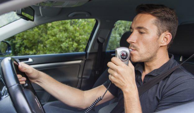 hombre_soplando_en_alcoholimetro_dentro_de_auto