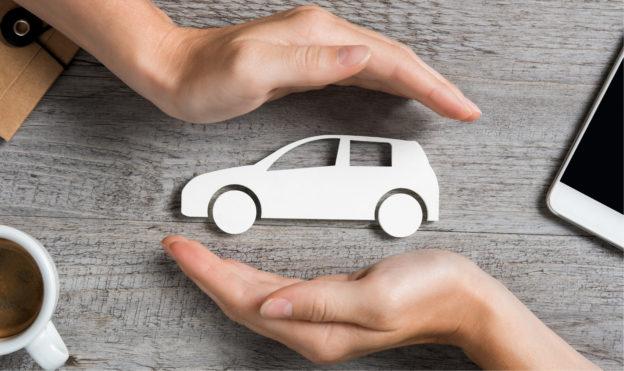 manos_cubriendo_auto_de_papel_sobre_mesa_seguro_de_auto