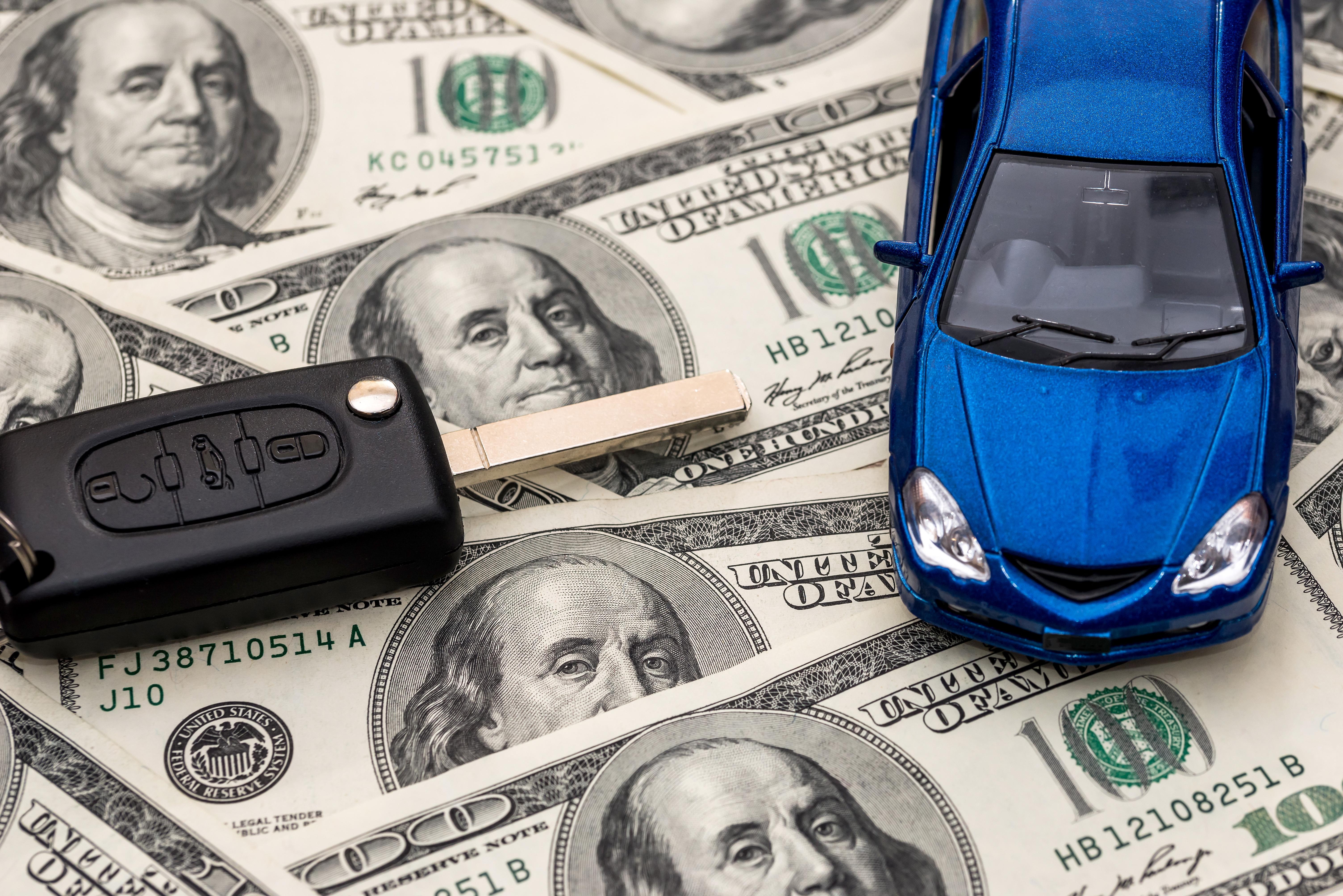 auto_azul_y_llaves_sobre_billetes_cien_dolares