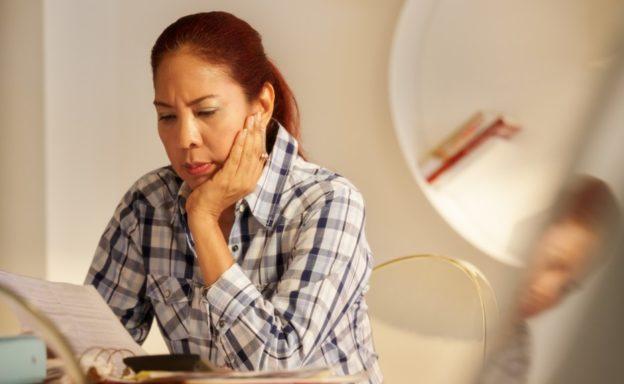 mujer latina viendo papel preocupada seguro sr22