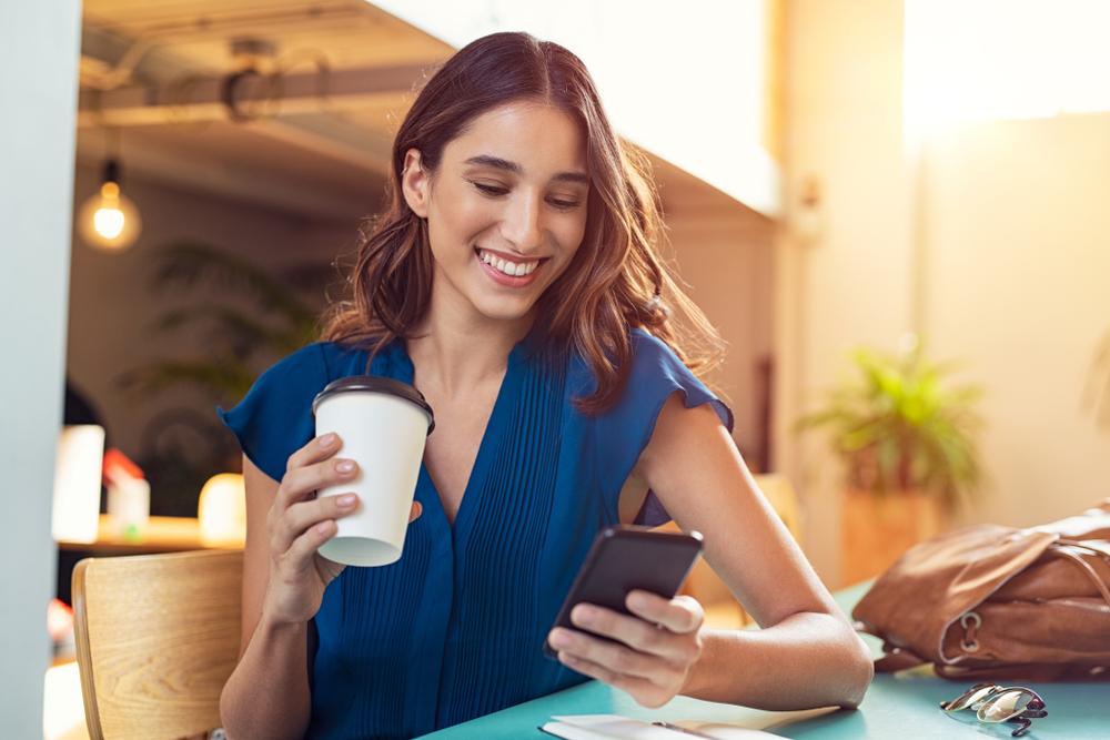 mujer latina feliz viendo su celular con cafe en la mano poliza de seguro de auto