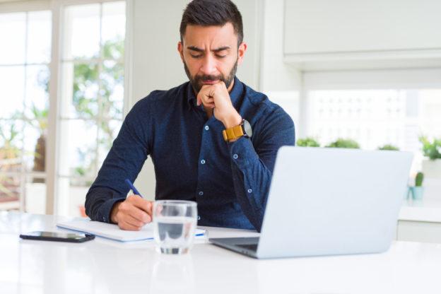 hombre latino confundido escribiendo en cuaderno frente a computadora seguro de auto