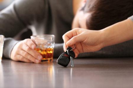 hombre ebrio sobre una mesa con una mano quitandole las llaves de su auto