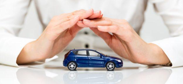 manos cubriendo auto azul de juguete sobre una mesa que es el seguro de auto