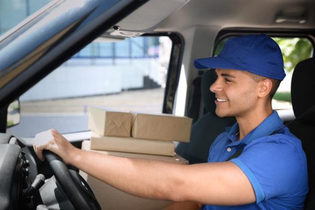 joven en su auto trabajando como repartidor con seguro de auto