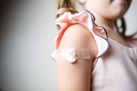 niña vacunada con algodón en el brazo las vacunas son gratis