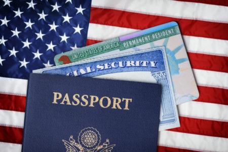 pasaporte, tarjeta de seguridad social y tarjeta de migracion sobre una bandera de estados unidos las consecuencias de un DUI