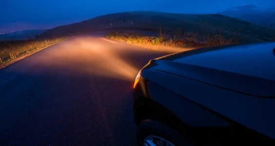 auto con los faros encendidos en carretera de noche