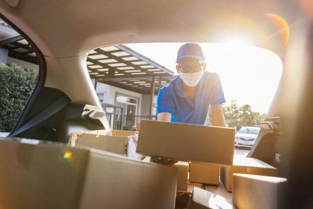 hombre repartiendo productos de amazon en su auto