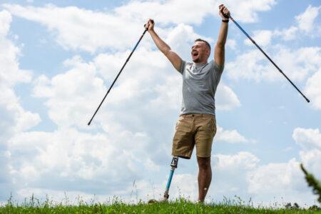 hombre con prótesis de pierna en un campo verde celebrando con los brazos alzados
