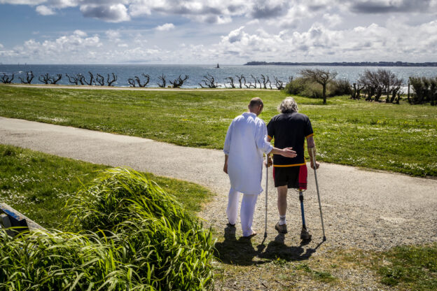hombre ayudando a persona mayor con prótesis de pierna caminar con muletas