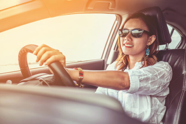 mujer con lentes de sol conduciendo auto nuevo con seguro