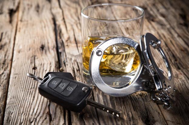 llaves de auto con una bebida alcoholica y esposas de policia sobre una mesa