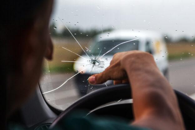 interior de un auto con el parabrisas roto con el conductor en el volante de fondo