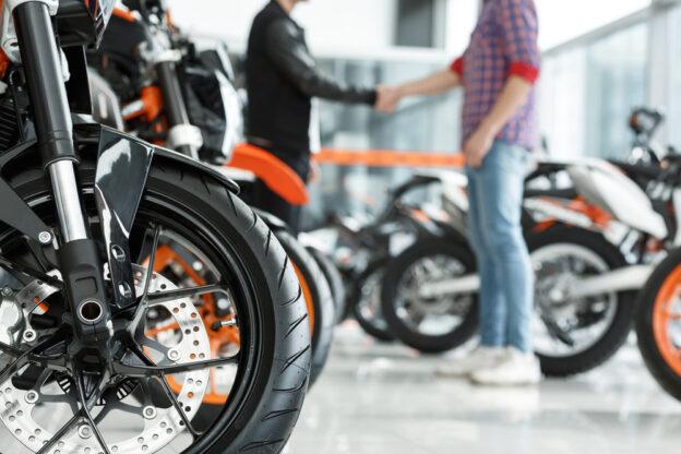 vista frontal de una moto con dos personas dandose la mano de fondo