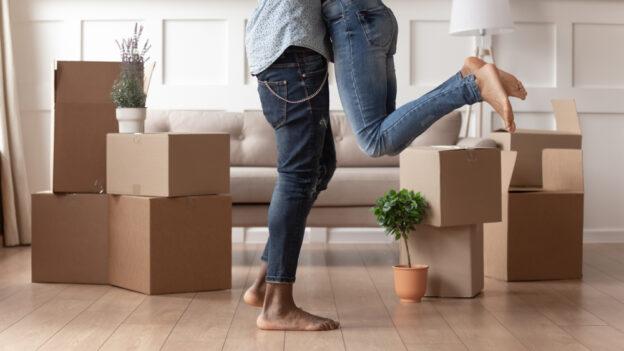 pareja feliz rentando su primer departamento en su sala con cajas de mudanza