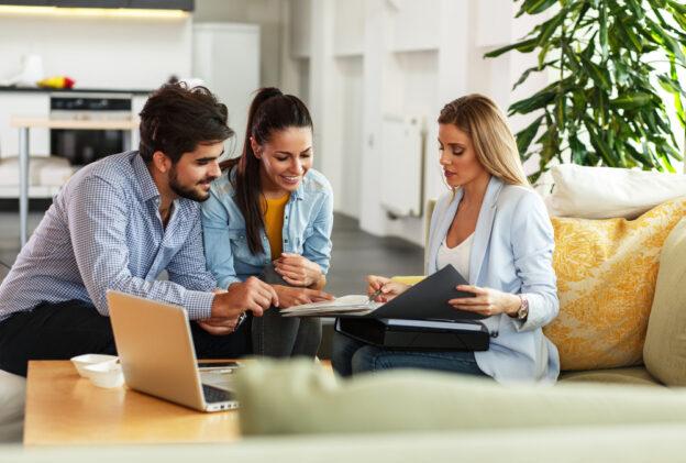 agente de seguro firmando una póliza de seguro de vida a una pareja