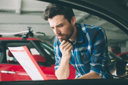 hombre joven revisando el historial del auto usado que va a comprar