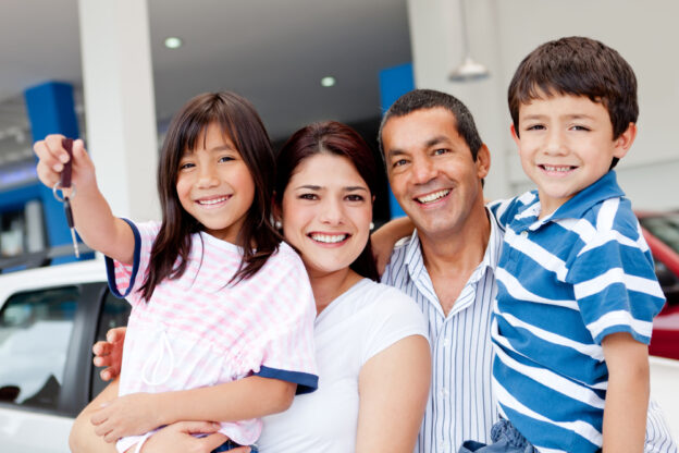 familia hispana feliz comprando un auto usado