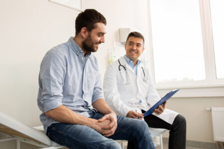 hombre hispano en consultorio con doctor y seguro medico con inscripcion abierta 2021