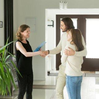 Mujer sonriente saludando de mano a una pareja joven y feliz dentro de un apartamento nuevo