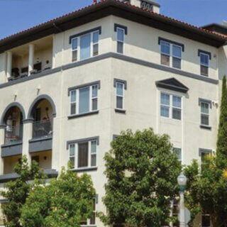 Unidad de apartamentos en un edificio colonial de color beige frente a unos arbustos