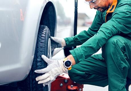 Mecánico agachado sosteniendo y cambiando la llanta de un automóvil de color gris