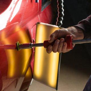 Mano de mécanico sosteniendo con fuerza un cilindro metálico para reparar un auto rojo