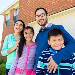 Familia de cuatro personas abrazados y sonriendo felices frente a su casa de ladrillos