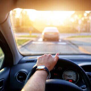 Vista frontal del interior de un auto con un conductor al volante en carretera