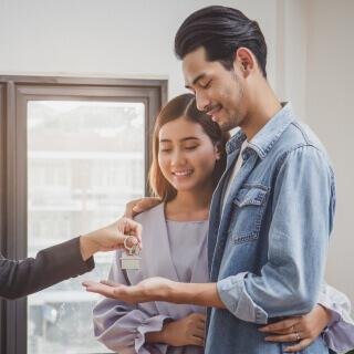 Una pareja de jóvenes recibiendo las llaves de su casa.