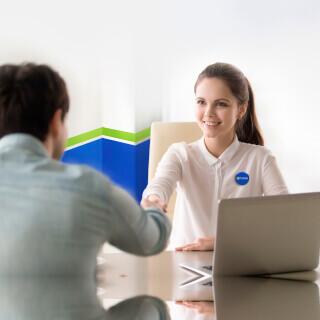 Una agente y un cliente estrechando las manos en la oficina de Freeway Insurance.