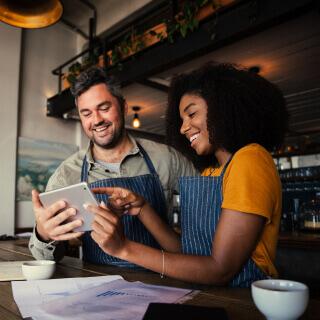 Dos dueños de un restaurante con el mismo delantal observan una tableta.