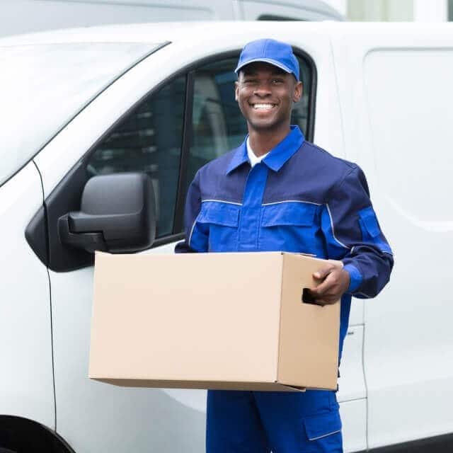 Un repartidor feliz sosteniendo una caja de cartón afuera de su carro.
