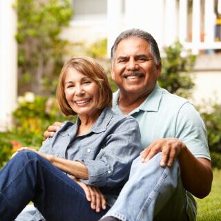 Una pareja feliz de mediana edad sentada en el patio trasero de una casa.